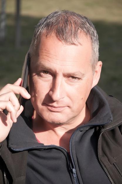Retrato de un hombre de pelo gris en una conversación a través del teléfono móvil. Foto Premium