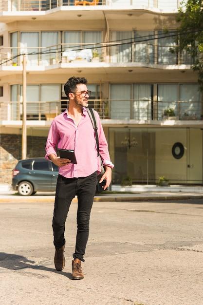 Retrato de un hombre que sostiene el diario en la mano caminando en la calle con su mochila Foto gratis