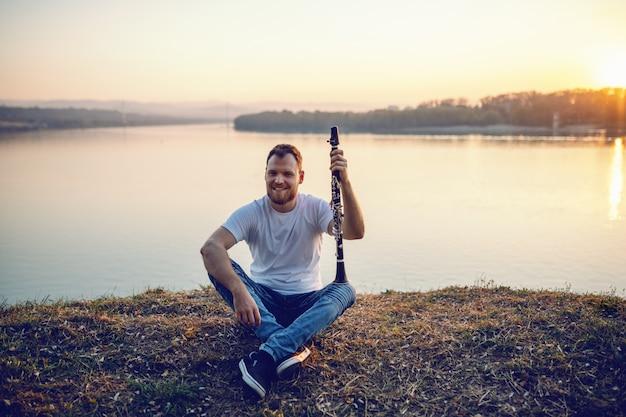 Retrato del hombre rubio barbudo caucásico sonriente hermoso que se sienta en el acantilado y que sostiene el clarinete. Foto Premium