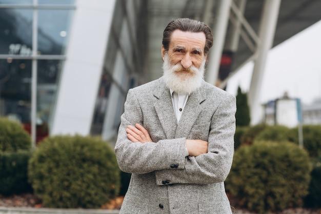 Retrato de hombre senior feliz con barba gris en los edificios de oficinas con espacio de copia Foto Premium