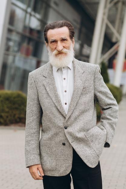 Retrato de hombre senior feliz posando en el edificio de oficinas Foto Premium