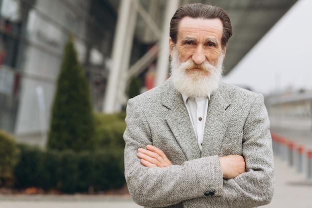 Retrato de hombre senior feliz posando en los edificios de oficinas Foto Premium
