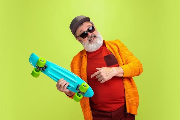 Retrato de hombre senior hipster sosteniendo un patín aislado sobre fondo verde. Foto gratis