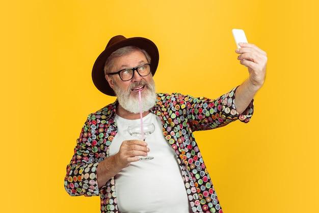 Retrato de hombre senior hipster usando dispositivos, gadgets aislados sobre fondo amarillo de estudio. tecnología y concepto de estilo de vida de ancianos alegre. Foto gratis