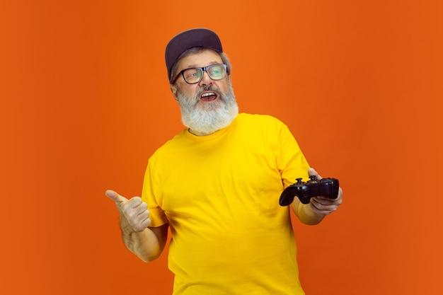 Retrato de hombre senior hipster usando dispositivos, gadgets aislados sobre fondo naranja studio. tecnología y concepto de estilo de vida de ancianos alegre. Foto gratis