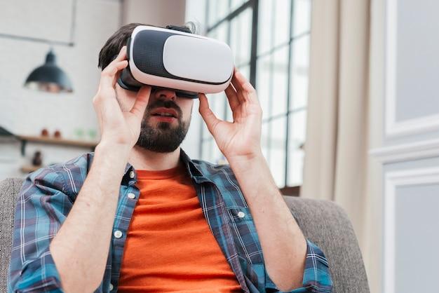 Retrato de un hombre sentado en el sofá con gafas de realidad virtual Foto gratis