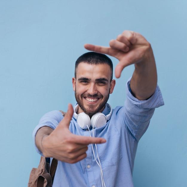 Retrato de hombre sonriente haciendo marco con su mano contra el fondo azul. Foto gratis