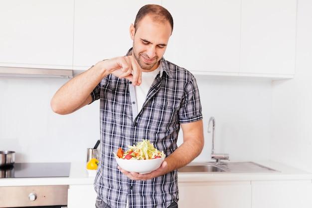 Retrato de un hombre sonriente que sazona la sal en la ensalada en la cocina Foto gratis