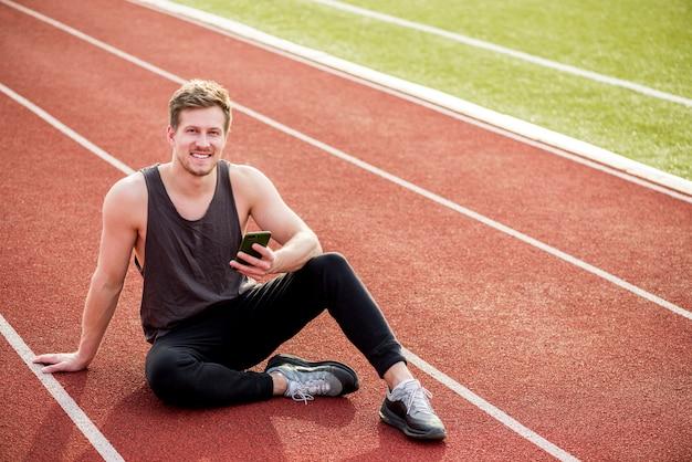 Retrato de un hombre sonriente sentado en la pista roja con teléfono móvil en la mano Foto gratis