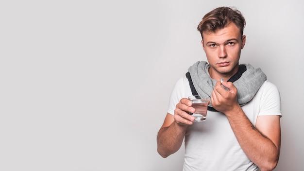 Retrato de un hombre tomando cápsula con agua sobre fondo blanco Foto gratis