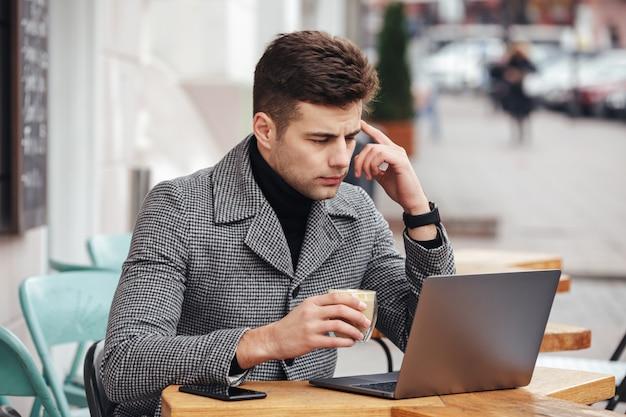 Retrato de hombre trabajador sentado con plata portátil en el café afuera, bebiendo americano de vidrio Foto gratis