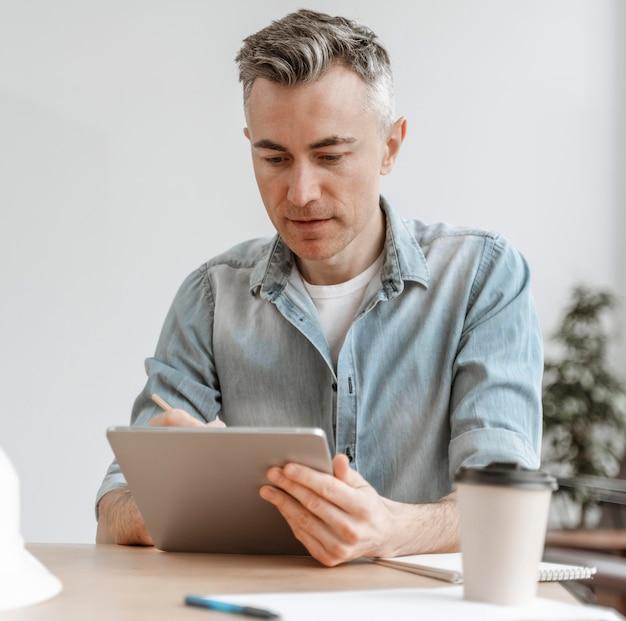 Retrato de hombre trabajando en tableta Foto gratis