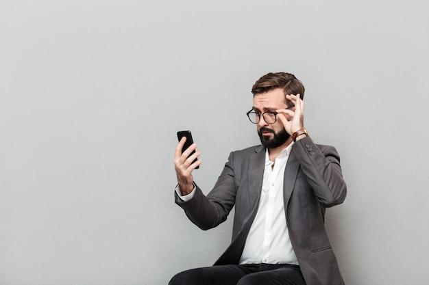 Retrato horizontal del empresario elegante mirando smartphone tocando anteojos mientras está sentado en la silla en la oficina, aislado en gris Foto gratis