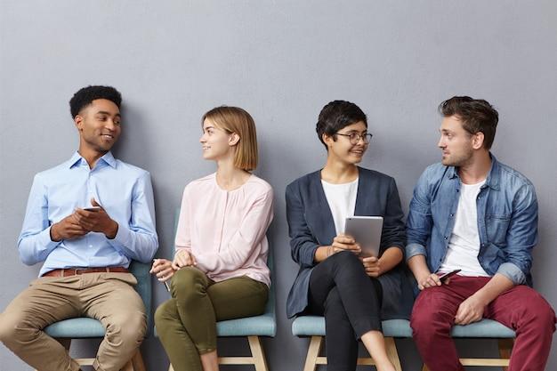 Retrato horizontal de personas que se sientan en cola, tienen una conversación agradable entre sí, Foto gratis