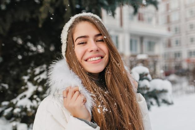 Retrato increíble mujer alegre con cabello largo morena en la nieve disfrutando del invierno en la calle. emociones brillantes, buen humor, sonrisa, felicidad, vacaciones de invierno. Foto gratis