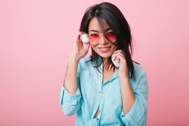 Retrato interior de una chica latina tímida con gafas de sol rosas escuchando música en grandes auriculares blancos. romántica dama asiática de pelo negro en camisa de algodón azul disfrutando de su canción favorita. Foto gratis