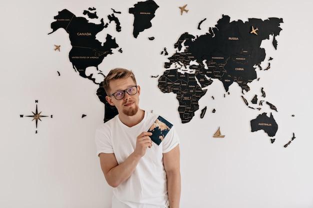 Retrato interior de feliz joven europeo con pasaporte posando sobre el mapa del mundo. preparándose para viajar, viaje de vacaciones. Foto gratis