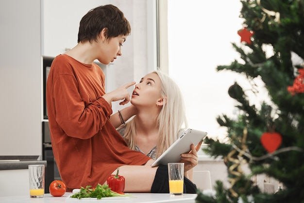 Retrato interior de la joven pareja sensual y tierna de chicas, expresando amor y atracción mientras está sentado en la cocina y sosteniendo la tableta en la mañana de navidad. la pareja de samesex coquetea y desayuna Foto gratis