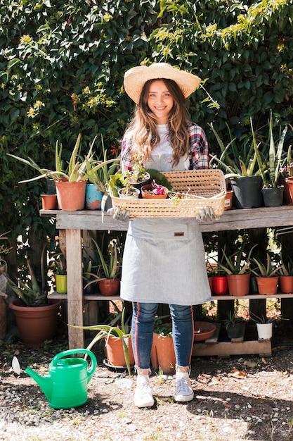Retrato de un jardinero femenino con sombrero sosteniendo la planta en maceta seleccionada en la cesta Foto gratis