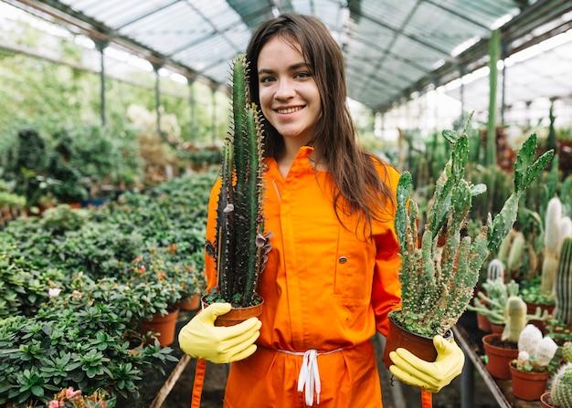 Retrato de un jardinero de sexo femenino joven sonriente que sostiene las plantas en conserva del cactus Foto gratis