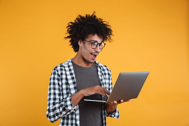 Retrato de un joven africano excitado en anteojos Foto gratis