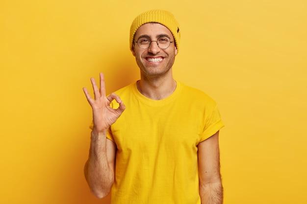 El retrato de un joven apuesto hace un buen gesto, demuestra que está de acuerdo, le gusta la idea, sonríe felizmente, usa gafas ópticas, sombrero amarillo y camiseta, modelos de interior. está bien, gracias. signo de mano Foto gratis