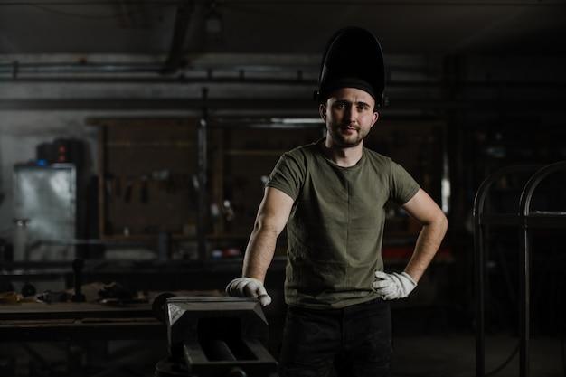 Retrato de un joven apuesto soldador masculino con una máscara protectora en la cabeza Foto Premium