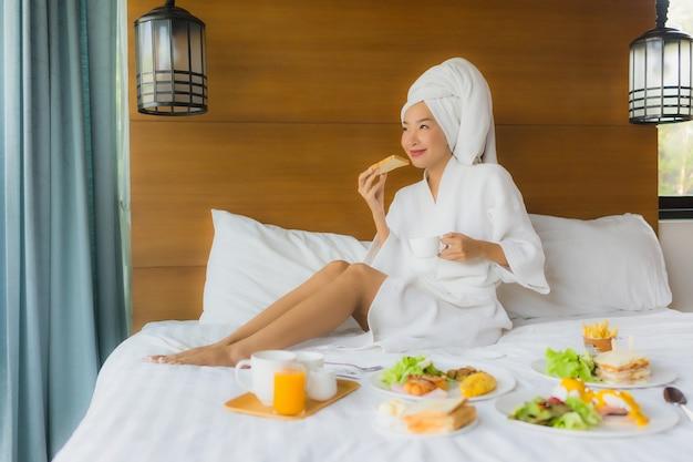 Retrato de joven asiática en cama con desayuno Foto gratis