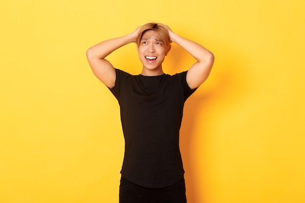 Retrato de joven asiático presa del pánico, mirando ansioso y molesto, tomados de la mano en la cabeza y haciendo muecas, de pie sobre una pared amarilla Foto gratis