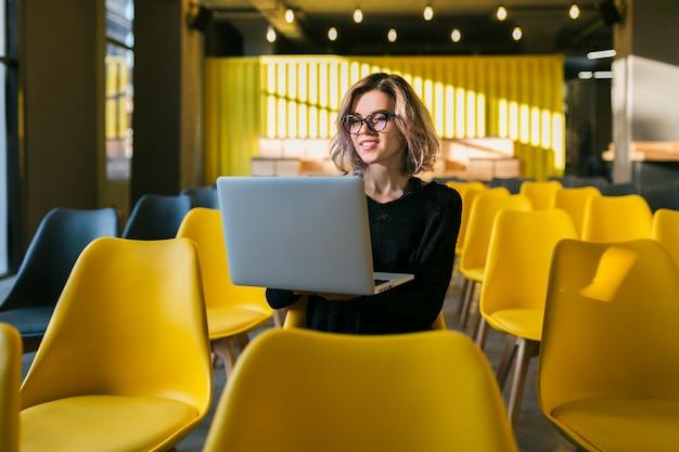 Retrato de joven atractiva mujer sentada en la sala de conferencias trabajando en la computadora portátil con gafas, estudiante aprendiendo en el aula con muchas sillas amarillas Foto gratis