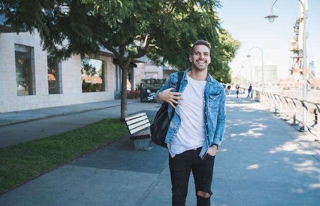 Retrato de joven atractivo caminando por la calle con mochila sobre los hombros. concepto urbano. Foto gratis