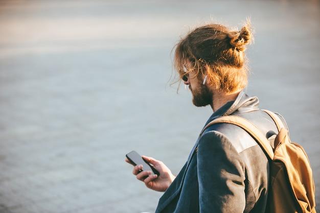 Retrato de un joven barbudo en auriculares Foto gratis