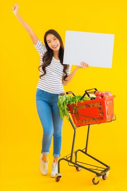 Retrato joven y bella mujer asiática con carrito de compras y mostrar tablero vacío blanco Foto gratis
