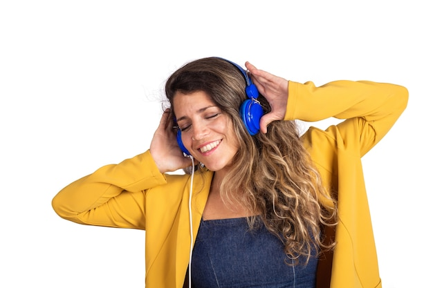 Retrato de joven bella mujer escuchando música con auriculares azules Foto gratis