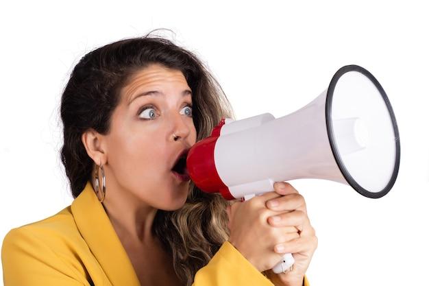 Retrato de joven bella mujer gritando en un megáfono aislado sobre fondo blanco. concepto de marketing o ventas. Foto Premium
