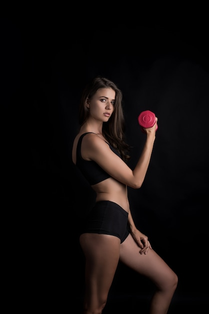 Retrato de joven bella mujer haciendo ejercicios físicos con pesas Foto gratis