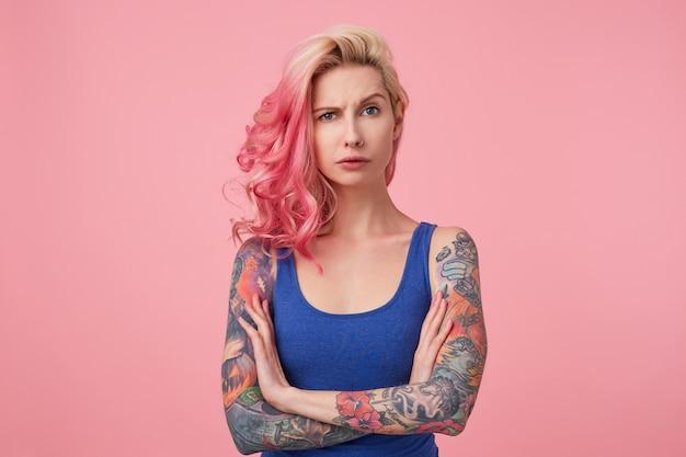 Retrato de joven belleza disgustada con cabello rosado, frunce el ceño y se para con los brazos cruzados, se ve triste, viste una camisa azul. concepto de personas y emociones. Foto gratis