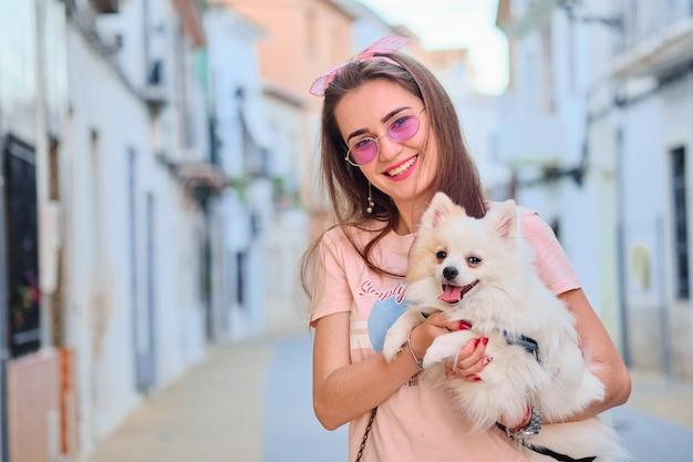 Retrato de una joven caminando con un pomerania esponjoso blanco. Foto Premium