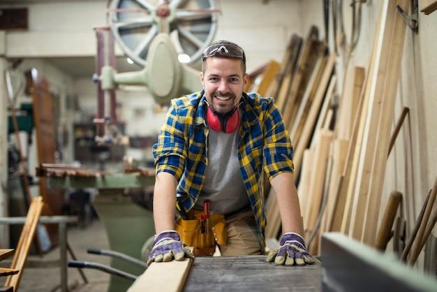 Retrato de joven carpintero motivado de pie junto a la máquina para trabajar la madera en su taller de carpintería Foto gratis