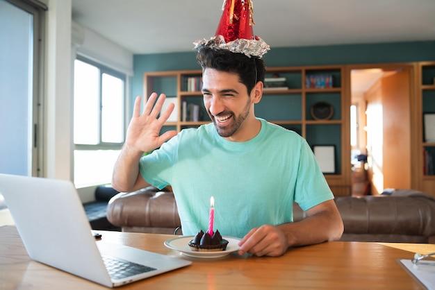 Retrato de joven celebrando un cumpleaños en una videollamada desde casa con un portátil y un pastel. nuevo concepto de estilo de vida normal. Foto gratis