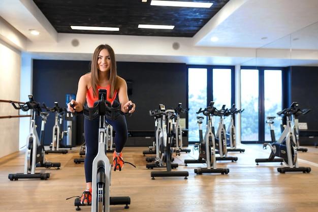 Retrato de joven delgada en ropa deportiva entrenamiento en bicicleta estática en el gimnasio. concepto de estilo de vida deportivo y de bienestar Foto Premium