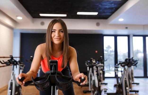 Retrato de joven delgada en ropa deportiva entrenamiento en bicicleta estática en el gimnasio Foto Premium