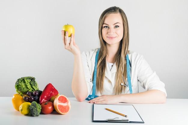 Retrato de una joven dietista femenina con manzana Foto gratis