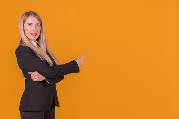 Retrato de una joven empresaria apuntando su dedo contra un fondo naranja Foto gratis