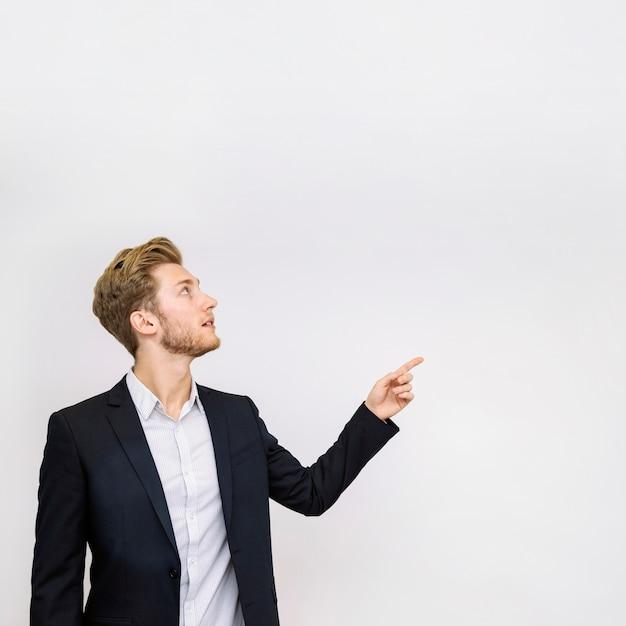Retrato de joven empresario apuntando a algo mirando hacia arriba Foto gratis