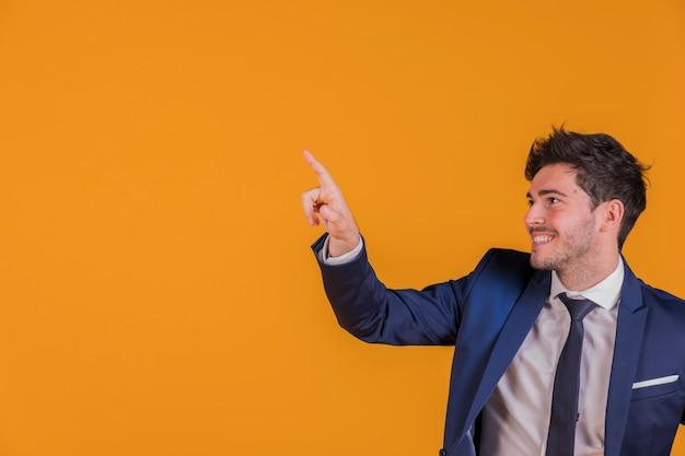 Retrato de un joven empresario apuntando su dedo contra un telón de fondo naranja Foto gratis