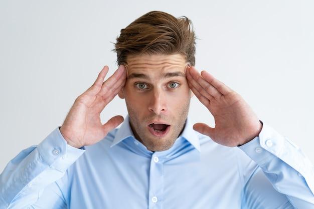 Retrato de joven empresario estresado masajeando la cabeza dolorida