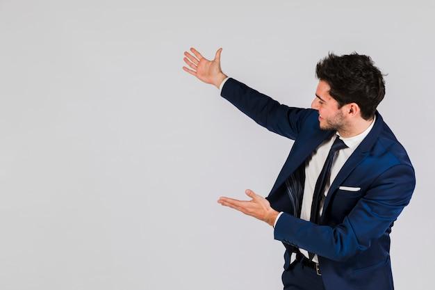 Retrato de un joven empresario presentando algo contra el fondo gris Foto gratis