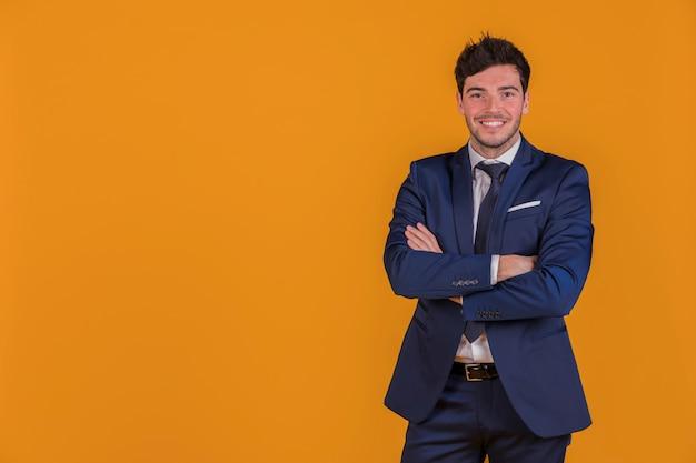 Retrato de un joven empresario con su brazo cruzado mirando a cámara Foto gratis