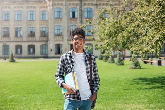 Retrato de un joven estudiante afroamericano hombre negro el fondo de la universidad. Foto Premium